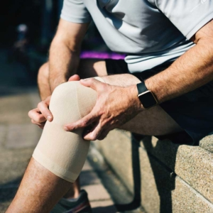 sitzender Mann mit Knie-Bandage