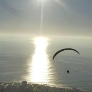 Paraglider gleitet vor einer Küste dem Sonnenuntergang entgegen